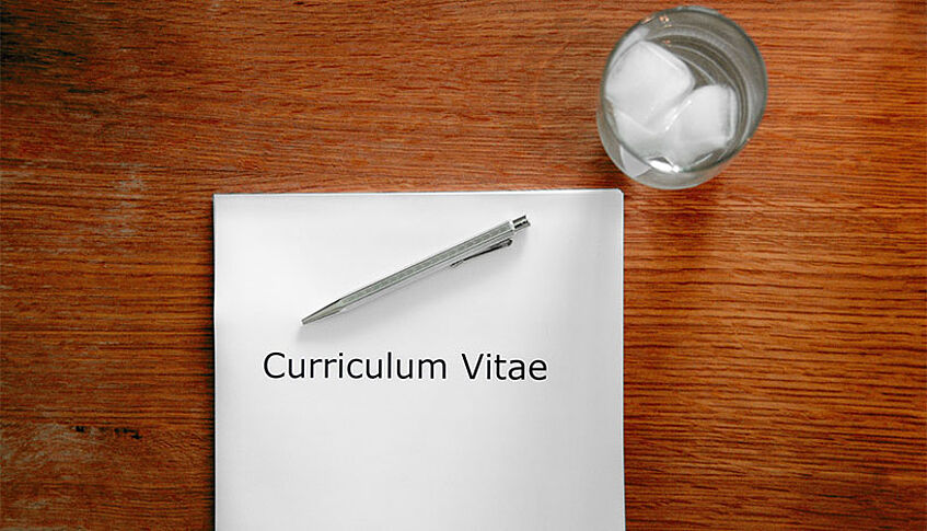 A CV, a pen and a glass of water on a table.